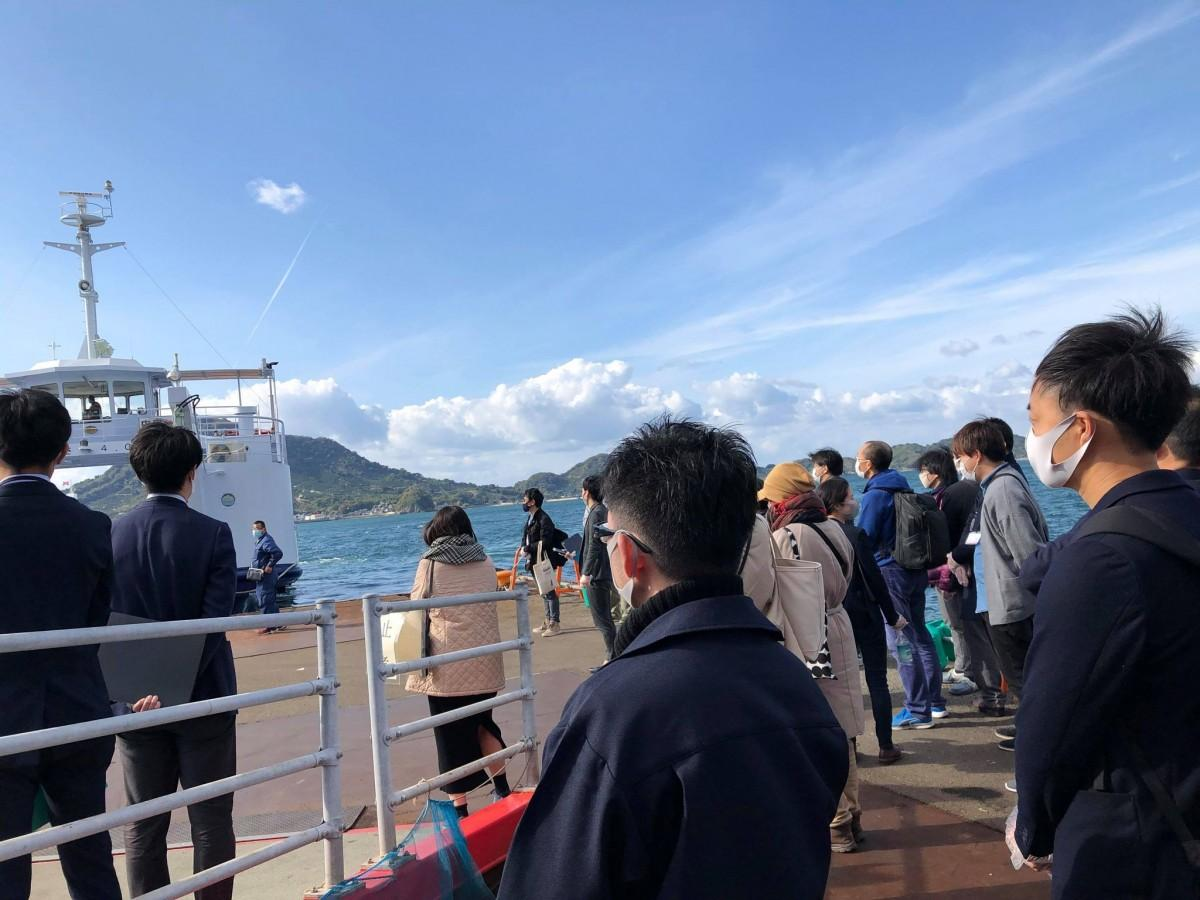 松山市で行ったフィールドワークの様子。興居島(ごごしま)行きフェリー乗り場で、参加者が企業ヒアリングを行った。