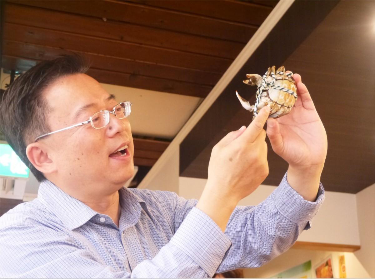 上海カニの食べ方をレクチャーする香約のオーナー馮文祥さん