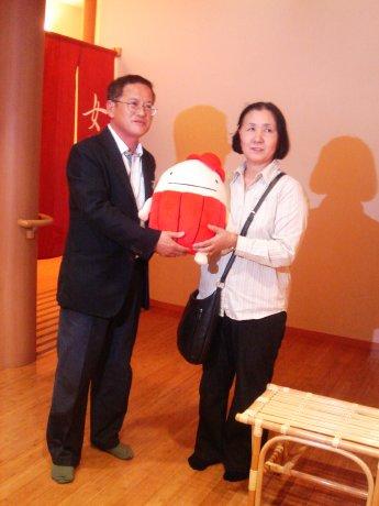 支配人の杉江さん(左)から記念品を受け取る50万人目の利用者、小島さん(右)