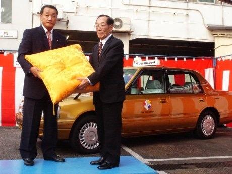 「金のフジタクシー」5,000人目の乗客となった松田さん(右)。同社の梅村会長(左)から記念品として「金の座布団」が贈られた