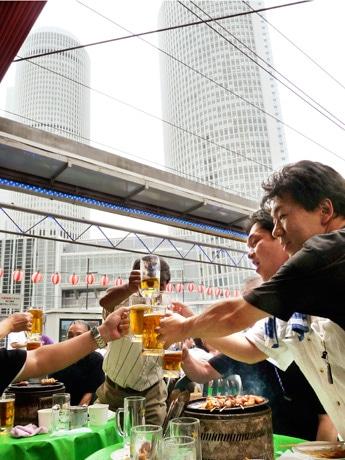 「ビアガーデン マイアミ」の目の前にそびえ立つJRセントラルタワーズをバックにビアガーデンを楽しむ利用客