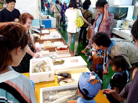 市場内を見学する子どもたちと、質問などに対応する店員ら