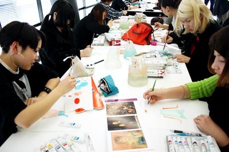 展覧会のパンフレットなどを参考に、ナナちゃん衣裳のデザインをするモード学園の学生たち