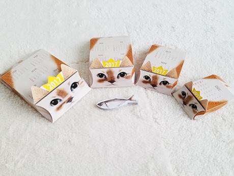 大きさ違いの四角い箱が4つ重なる「ネコリョーシカカレンダー」。真ん中には付属の魚型の付箋