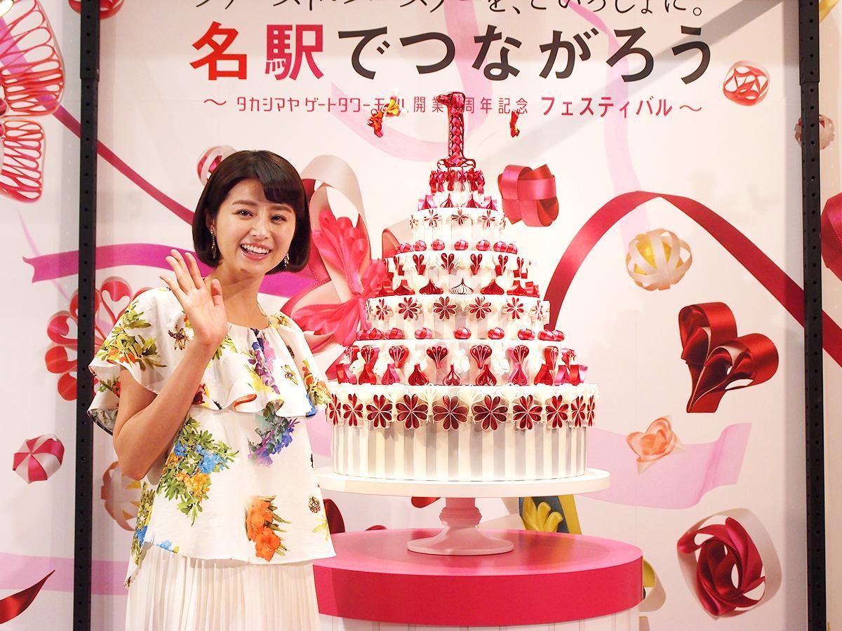 バースデーケーキをモチーフにしたリボンのアート作品の前で鈴木ちなみさん