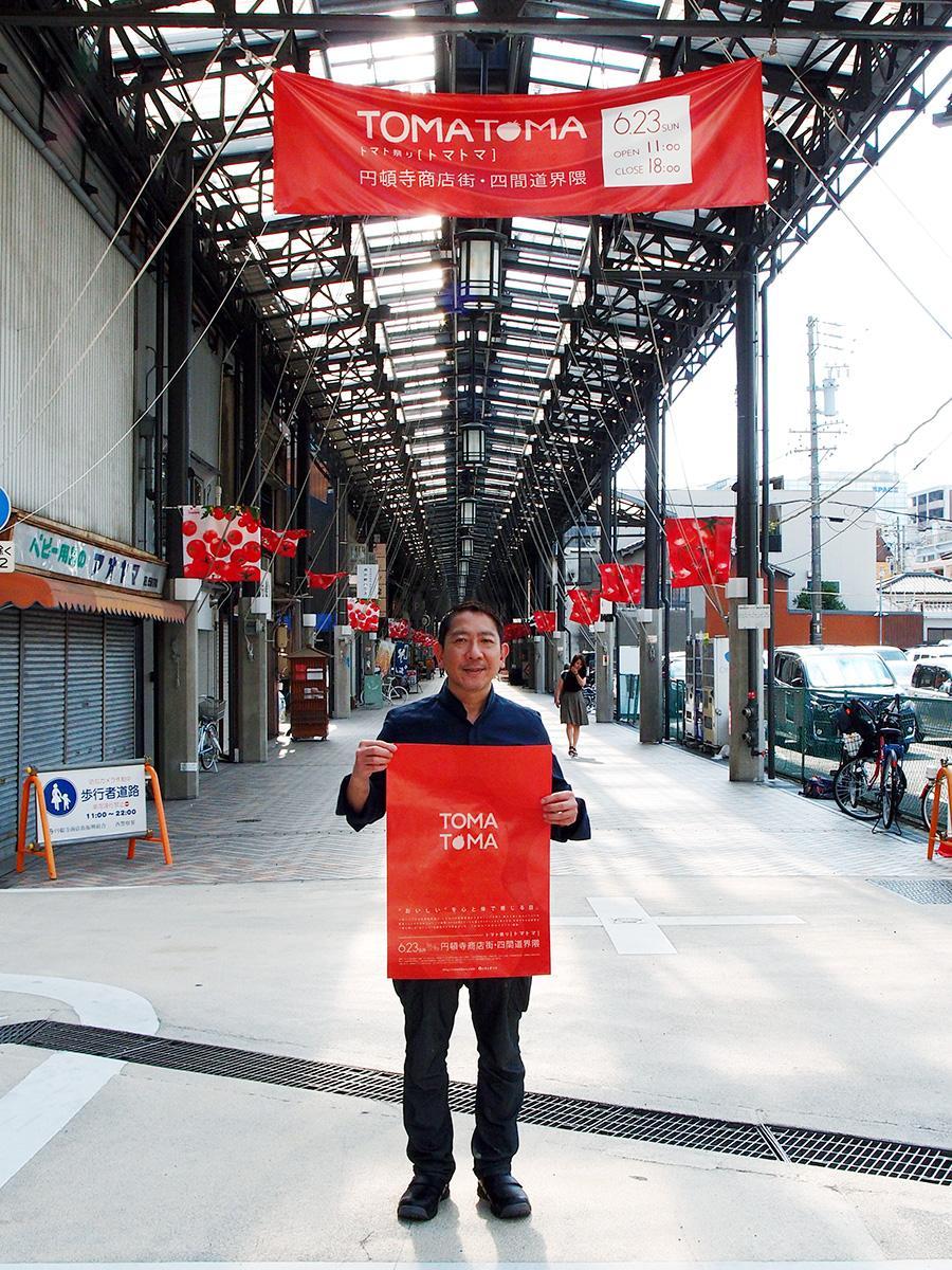 「トマトマ」のポスターを手にした、企画者で「四間道レストランMATSUURA」オーナーシェフの松浦さん