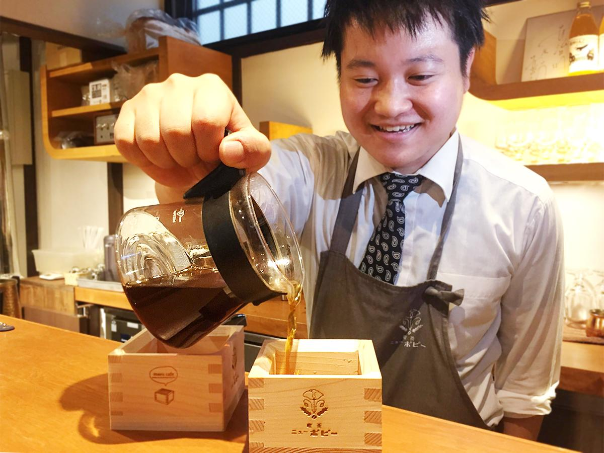 ヒノキ香る升に開発したコーヒー「枡プレッソ」を注ぐ岸田さん