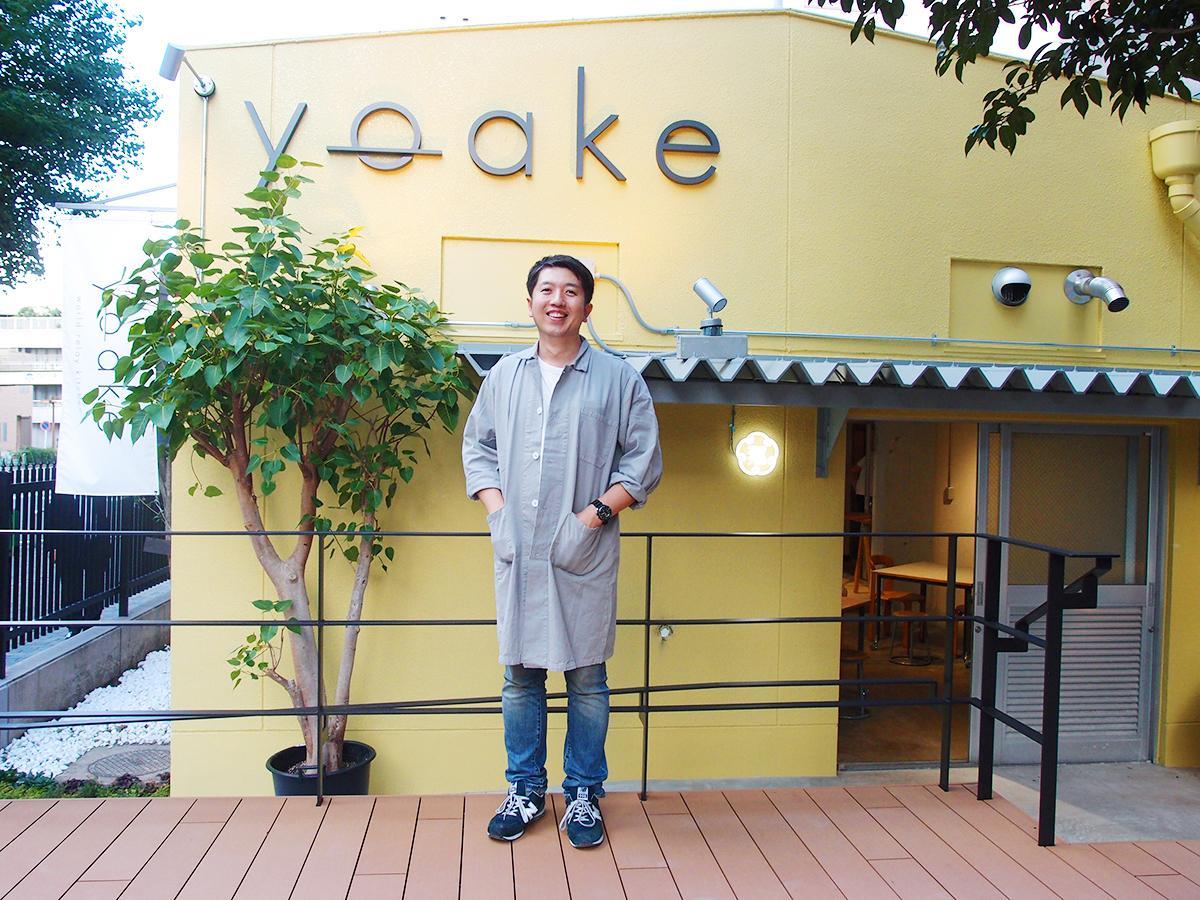 「yoake」を運営する「ホリデイズ」社長の落合裕一さん。給食室をリノベーションした店舗の前。