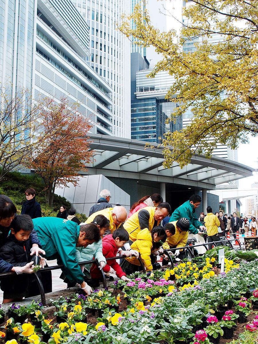 名古屋駅地区街づくり協議会と園児らの花植え作業の様子