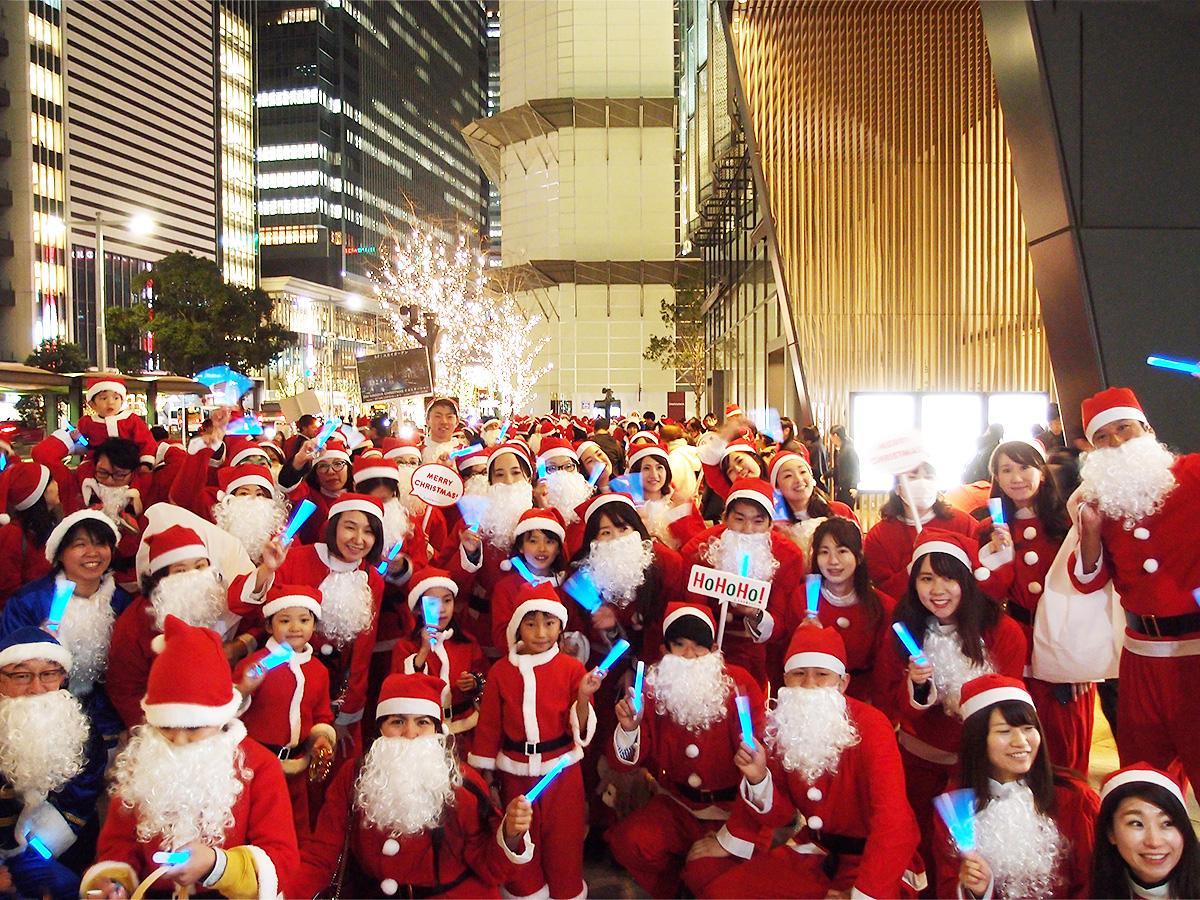 名古屋駅前の「大名古屋ビルヂング」前で記念撮影に応える「サンタクロース」たち