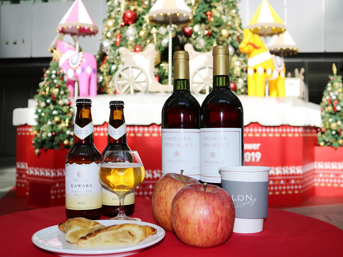 クリスマスツリー横のカフェスタンドで販売するアップルパイやビールのイメージ