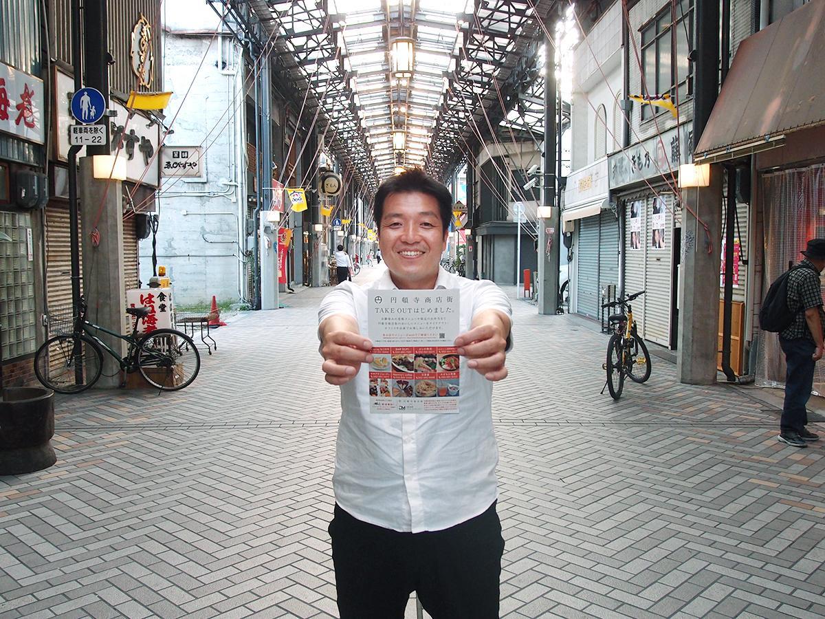 「円頓寺商店街TAKE OUT」のチラシを手に円頓寺商店街理事長の田尾大介さん