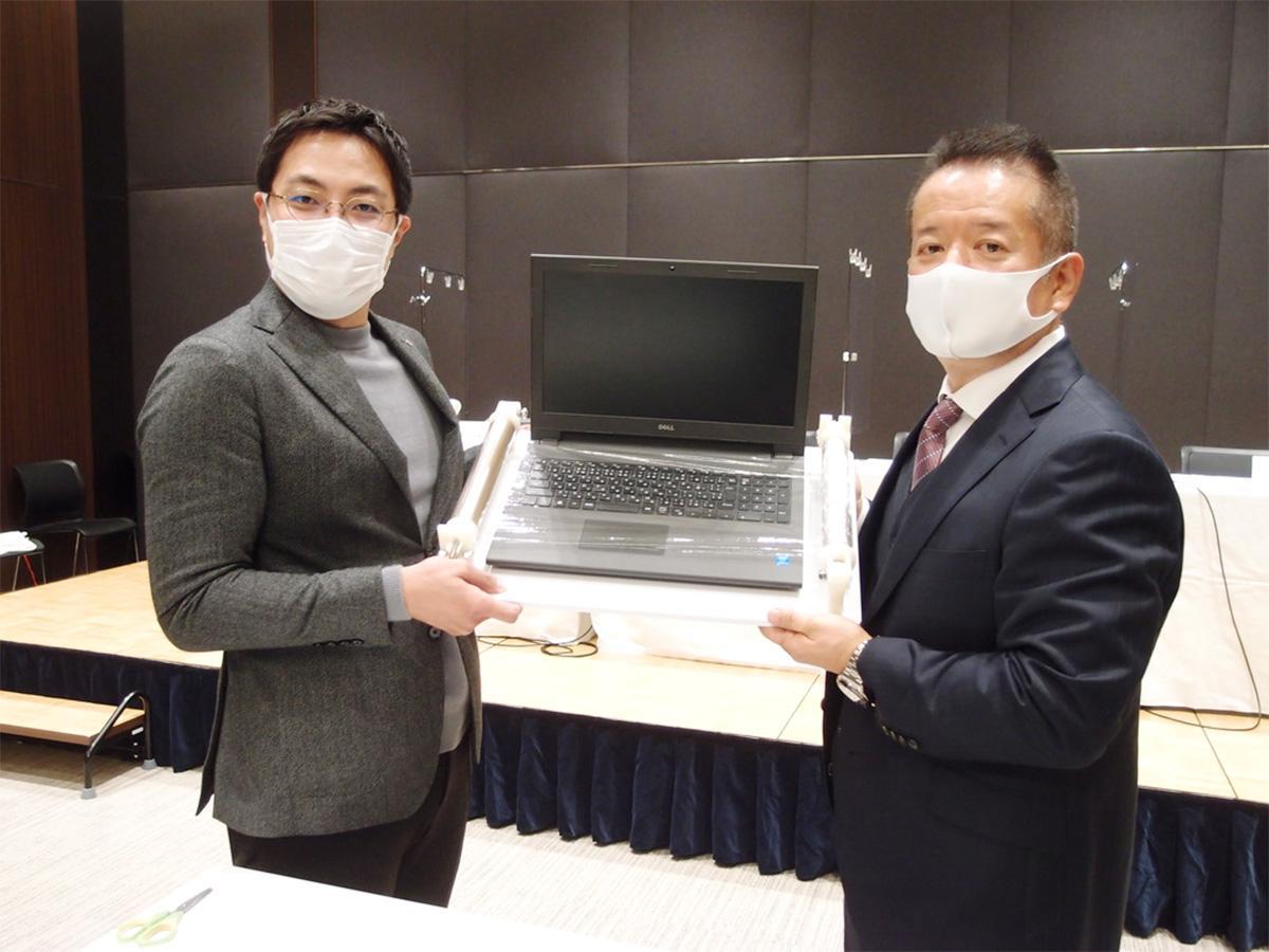 製品「タッチラップ」を使いラップフィルムでキーボードを覆った状態を披露する、自身も医師である「エムエス製作所」の迫田邦裕社長(左)と「山一ハガネ」の寺西基治社長(右)