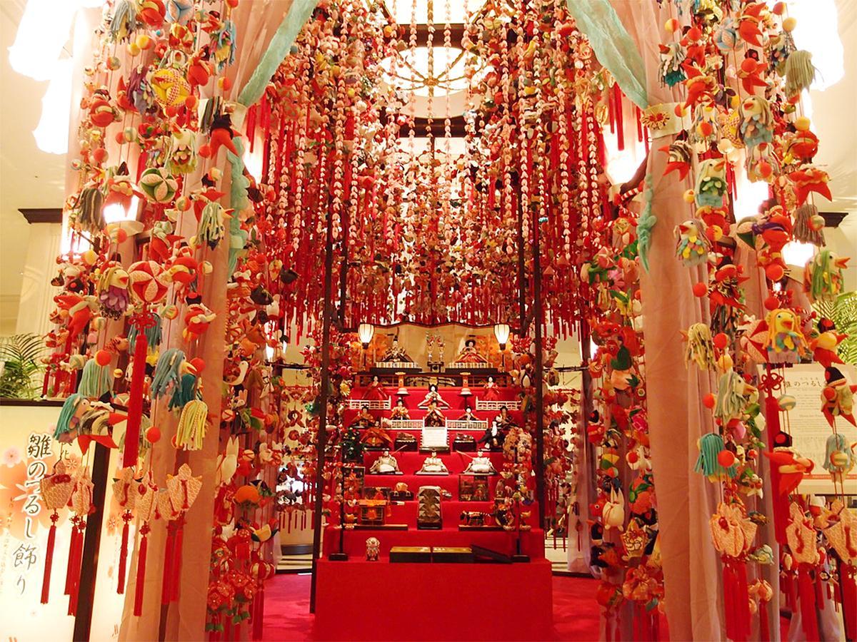 「名古屋マリオットアソシアホテル」に展示中の「雛のつるし飾り」。ひな人形の段飾りを囲み、1万588個のひなと有松・鳴海絞の麻の葉模様のレースカーテンが飾られる
