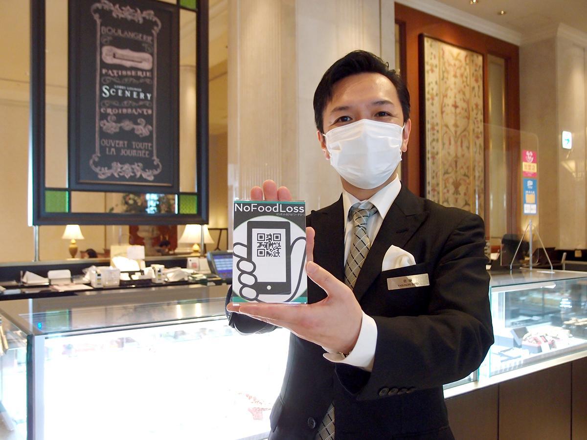 アプリ「No Food Loss」のPOPを手にする、名古屋マリオットアソシアホテルのロビーラウンジ「シーナリー」マネジャーの佐藤保哲さん
