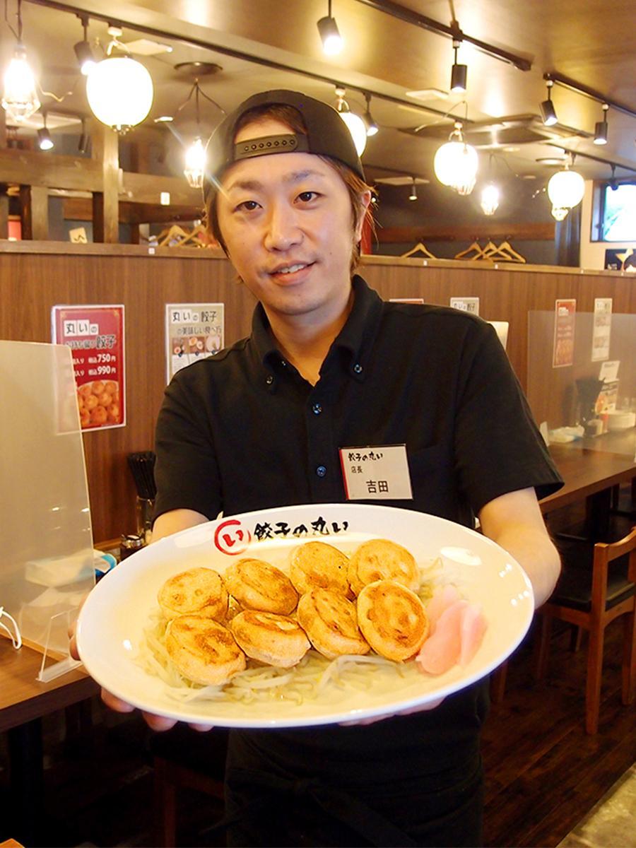 「丸いの餃子」を手にする店長の吉田修平さん