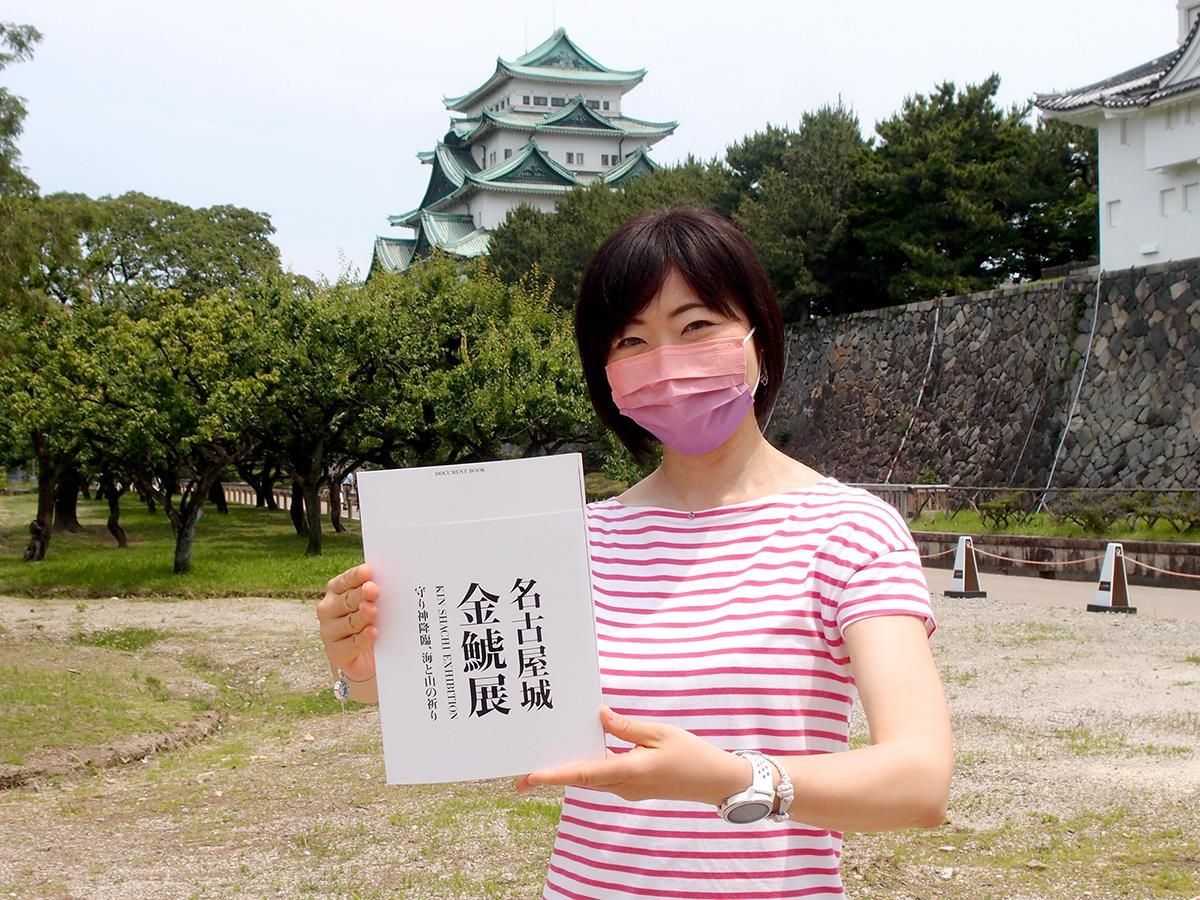 金しゃち不在の天守閣前で、「名古屋城金鯱展」のドキュメントブックを手にする西浦さん