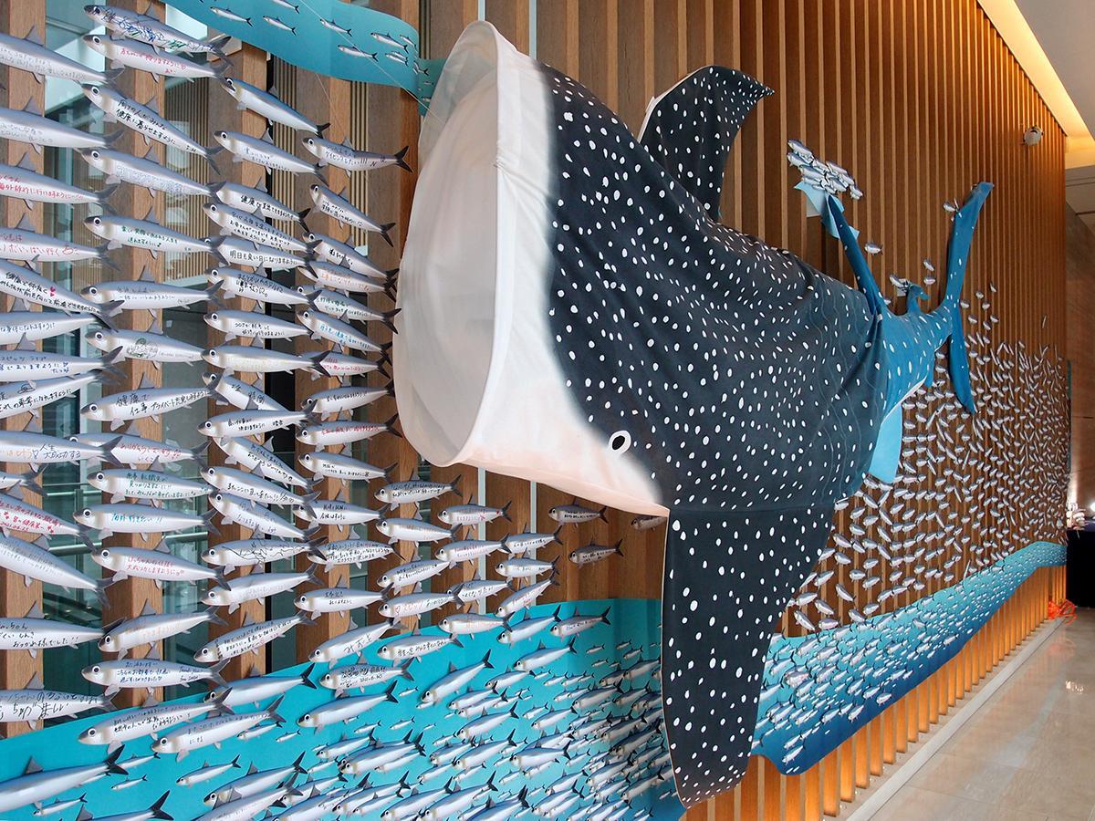 全長5.17メートルの手染めのジンベイザメ。ジンベイザメが願い事・困りごとを書き込んだイワシ型短冊を吸い込むように展示されている