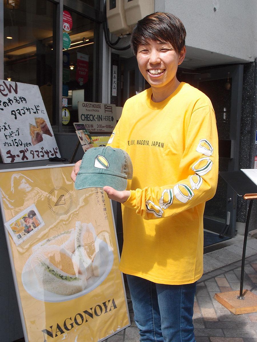 「なごのや」のタマゴサンドのポスター前で、「タマゴサンドコレクション」を紹介する嶋本紗季里さん