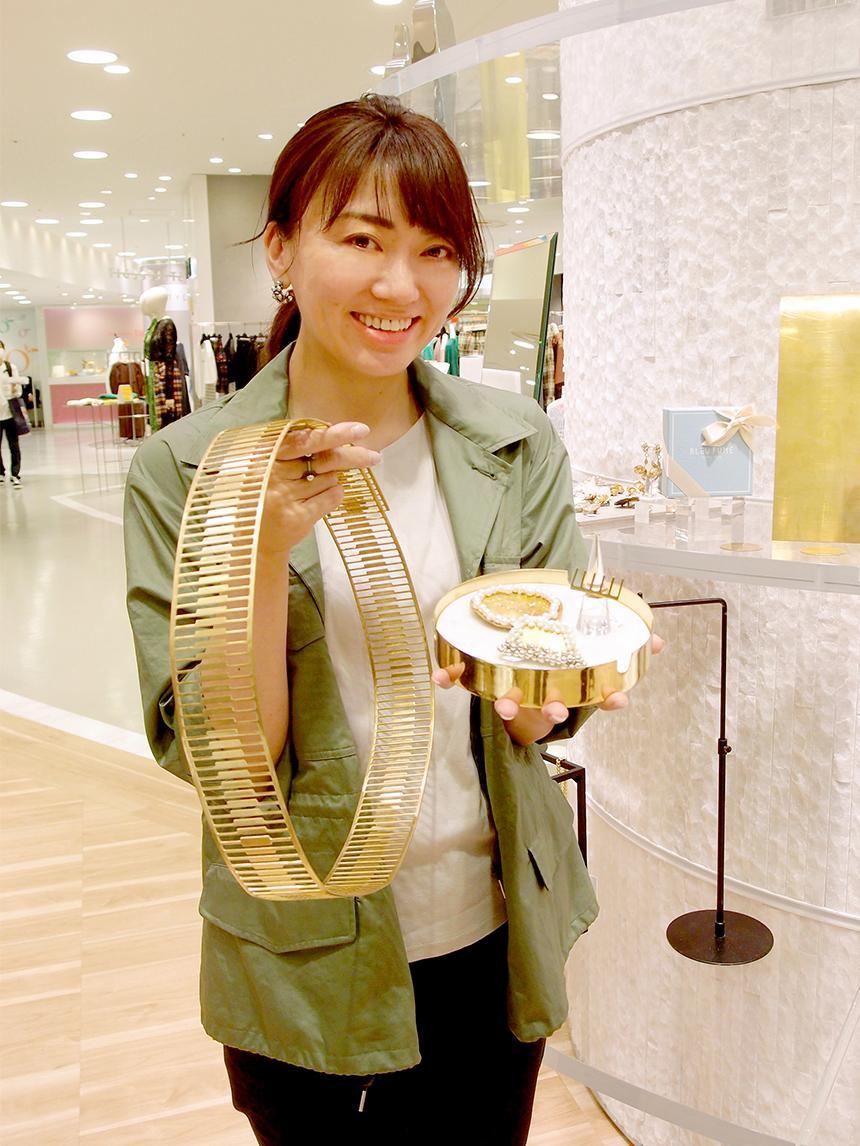 廃材の真ちゅうを使ったアクセサリーと、材料の廃材の真ちゅうを右手で持つNatsukoさん