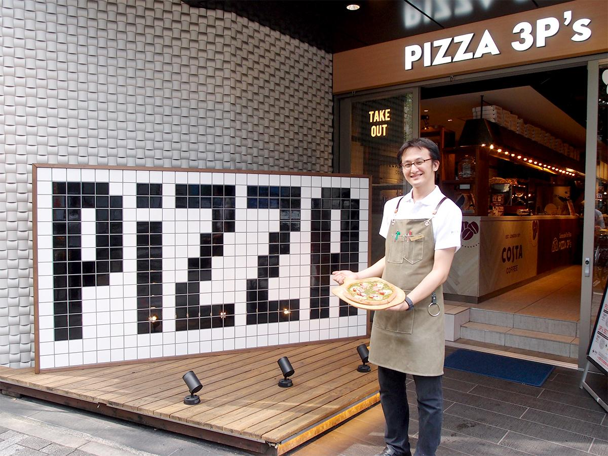 「PIZZA 3P's」店舗前で「お薦め」のカスタマイズピザを手にする店長の藤崎昭博さん