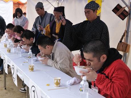 「第10回水戸納豆早食い世界大会」でネバネバ納豆の早食いに挑む挑戦者たち