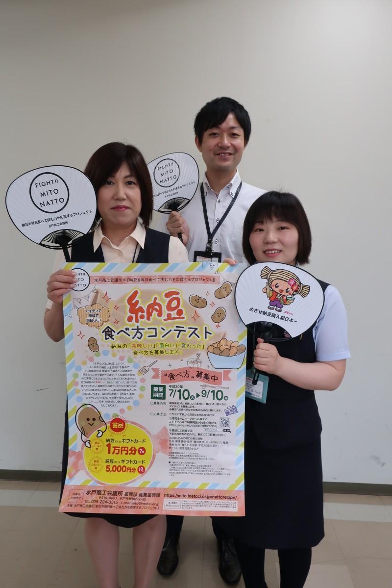 イベントポスターを持つ商工会議所の担当者
