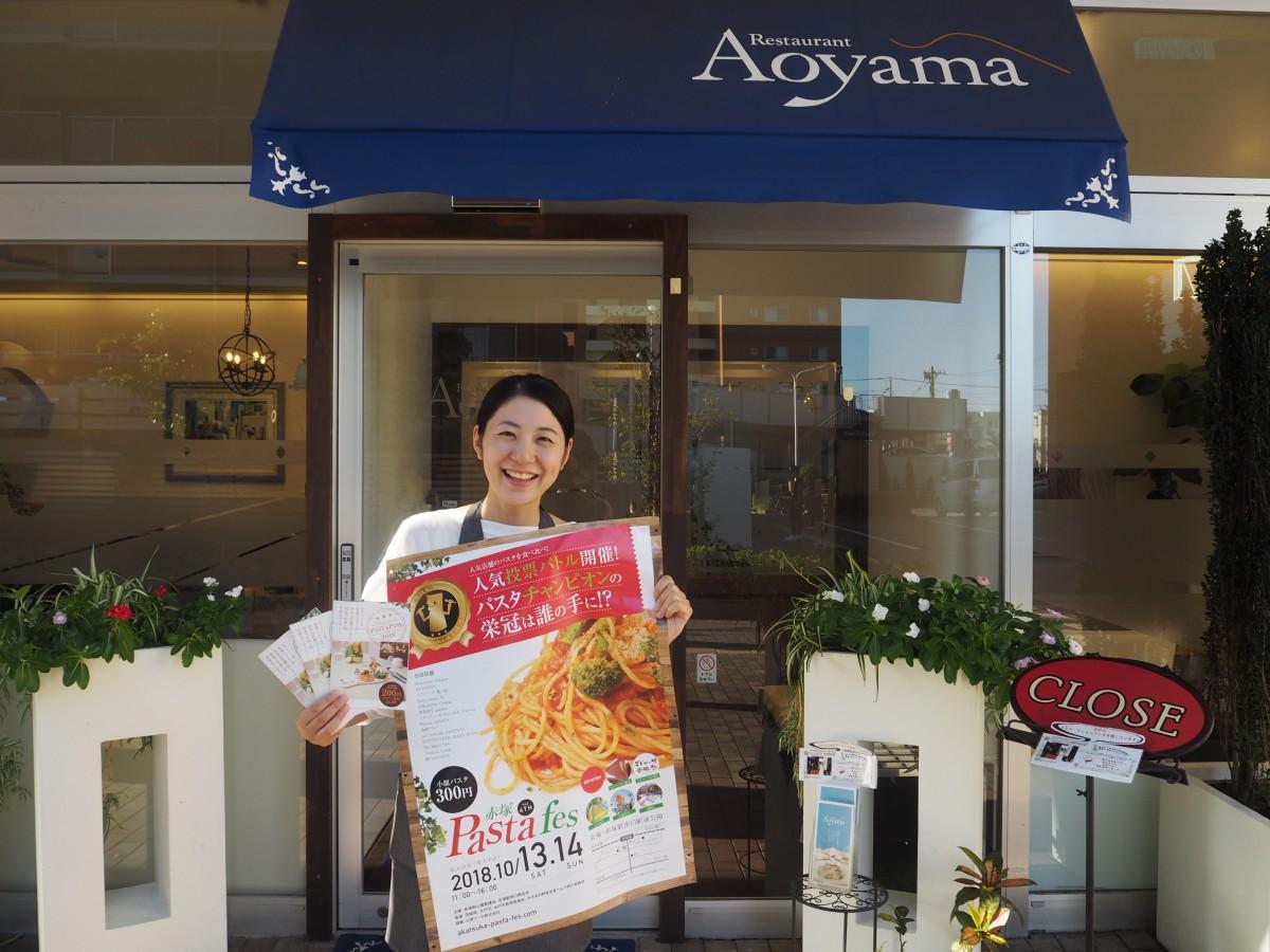 イベントポスターを手に笑顔を見せる青山さん
