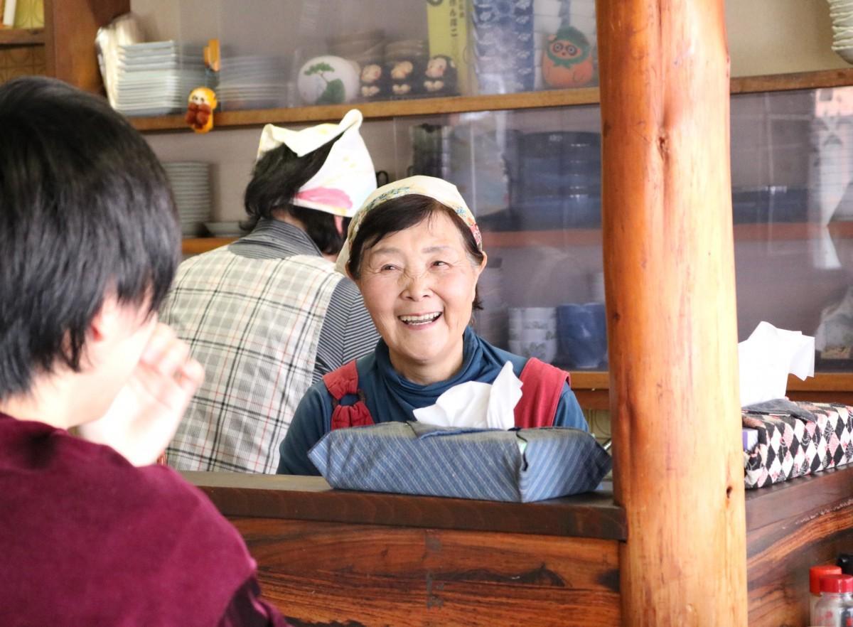 厨房(ちゅうぼう)に立ち笑顔を見せる小林美智子さん