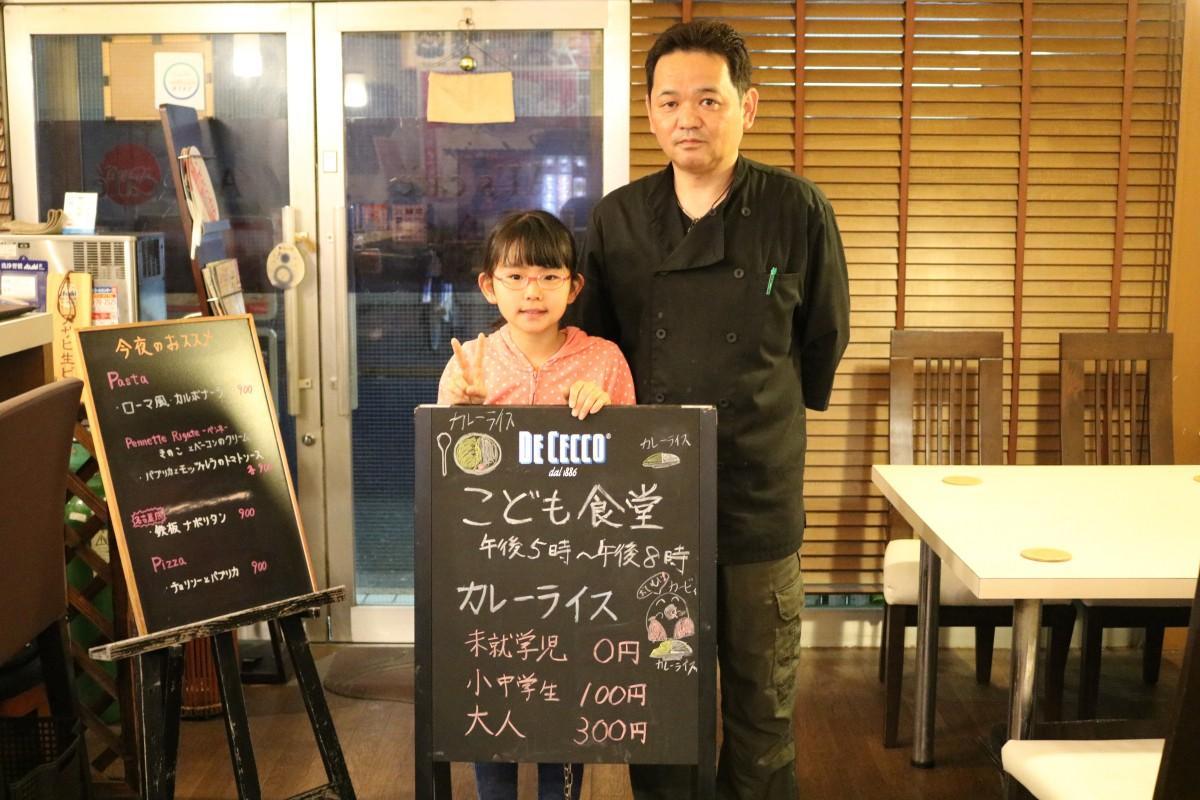看板を前に立つオーナーの石田健一さんと娘のゆいかちゃん