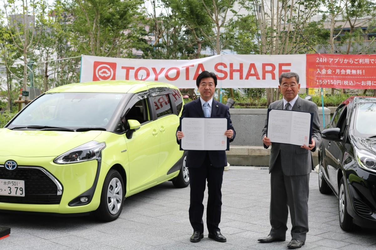 車両前で協定書を持つ高橋靖市長(左)と「茨城トヨペット」幡谷定俊社長(右)