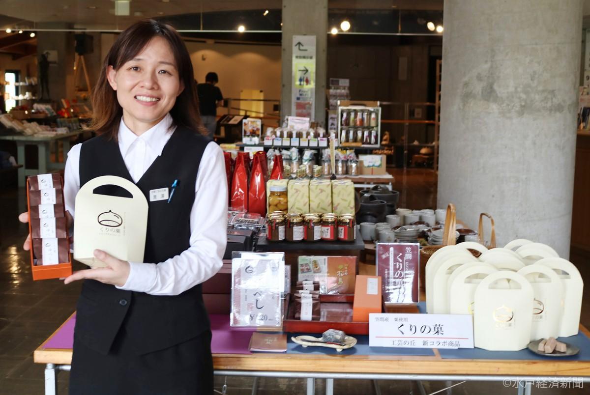 「くりの菓」シリーズの「クランチチョコ」と「栗ゆべし」を手に笑顔を見せる黒澤さん