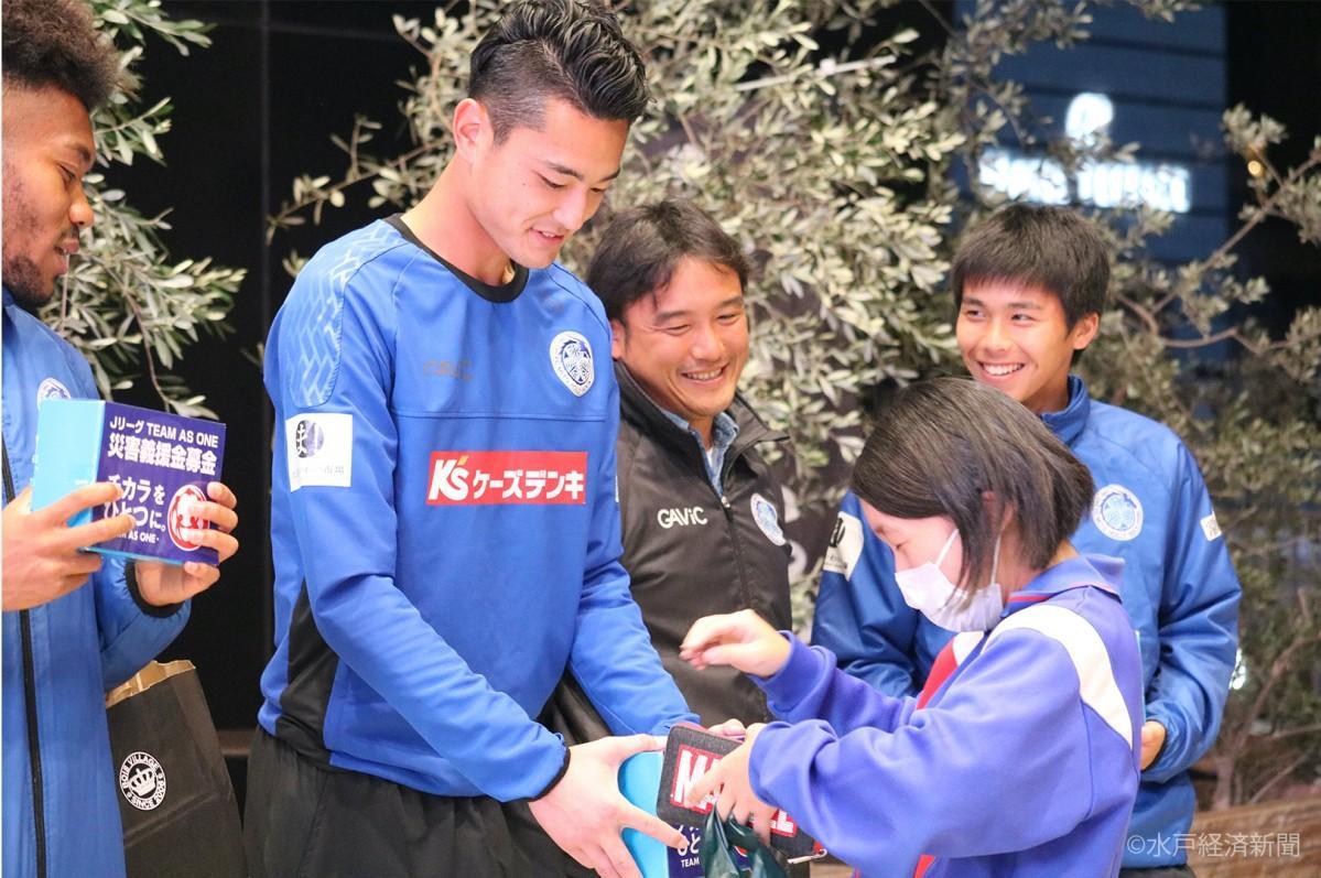 水戸駅で募金を呼び掛けるホーリーホック選手と募金を行う女子中学生