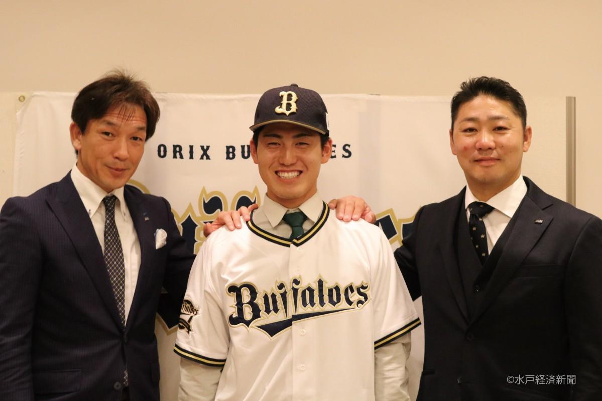 (左から)牧田チーフスカウト、ユニホームに袖を通し笑顔を見せる鶴見凌也選手、上村スカウト