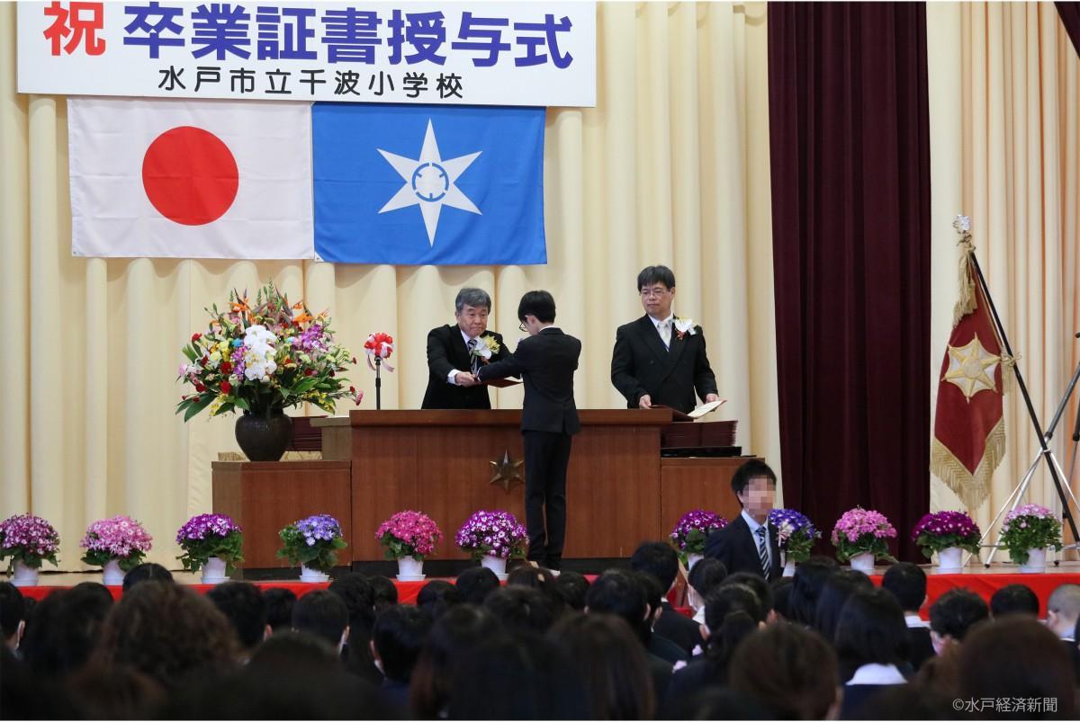 壇上で児童一人一人に卒業証書を手渡す和田雅彦校長と宇野博樹教頭