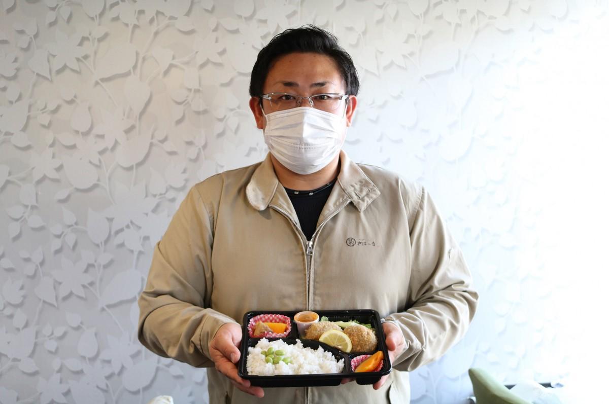 弁当を手にする海老澤店長