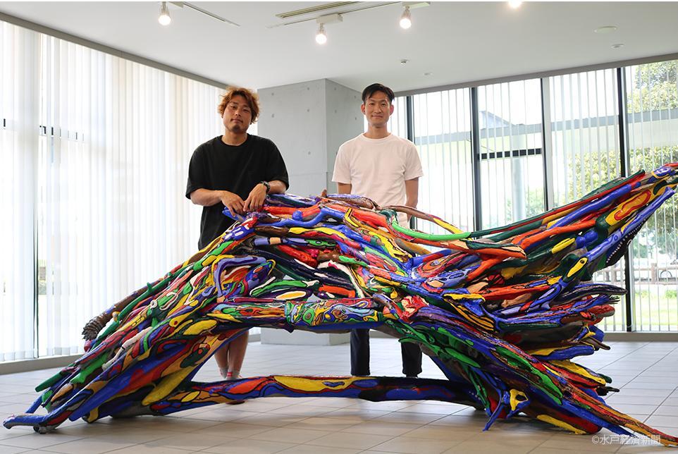 (左から)「青いベンチ」を前にするアーティストの桐原さん、地域おこし協力隊の坂本さん