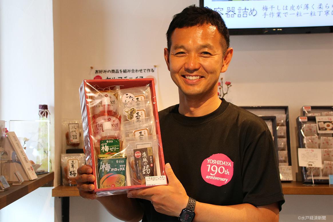 「190周年記念ギフト」を手に笑顔を見せる大山さん