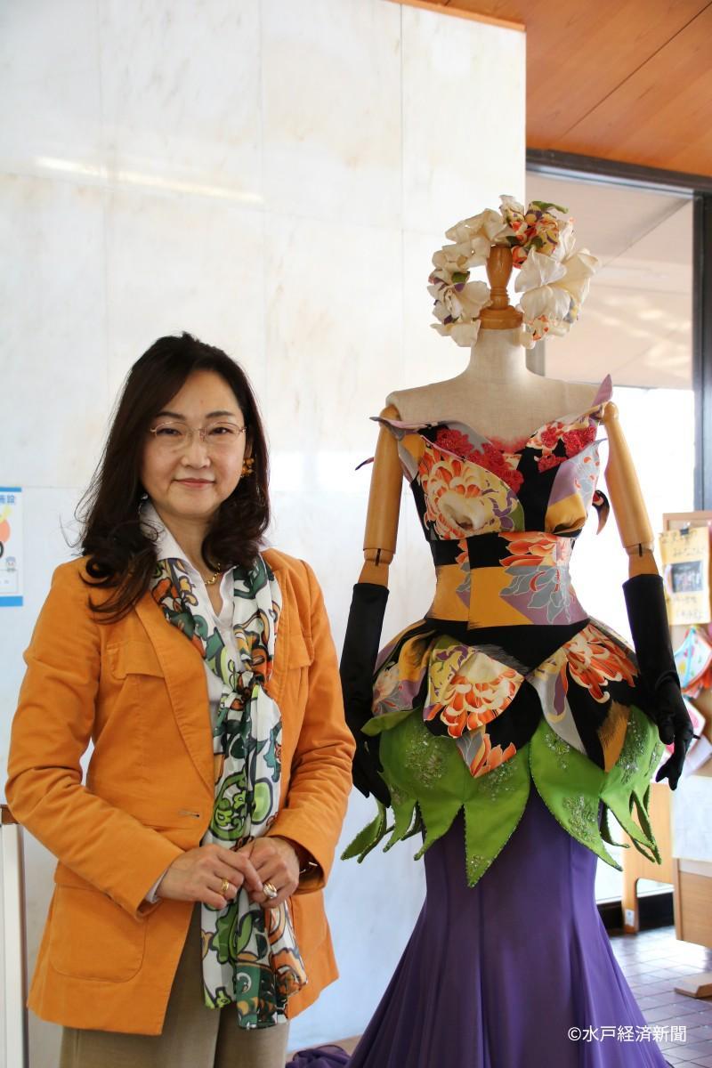 制作した着物ドレスを前にほほ笑む川澄さん