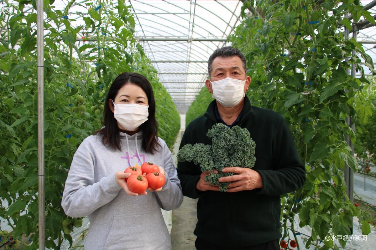 那珂市産野菜を手にする那珂市地域おこし協力隊の入江さん、綿引会長