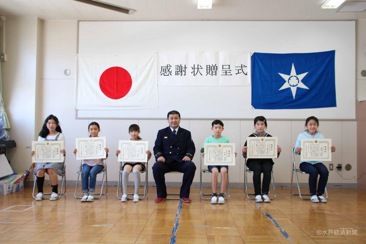 青木署長(中央)と感謝状を手に笑顔を見せる6人
