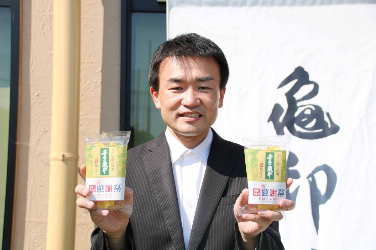 コラボパッケージの「吉原殿中」を手にする亀印製菓の脇田社長