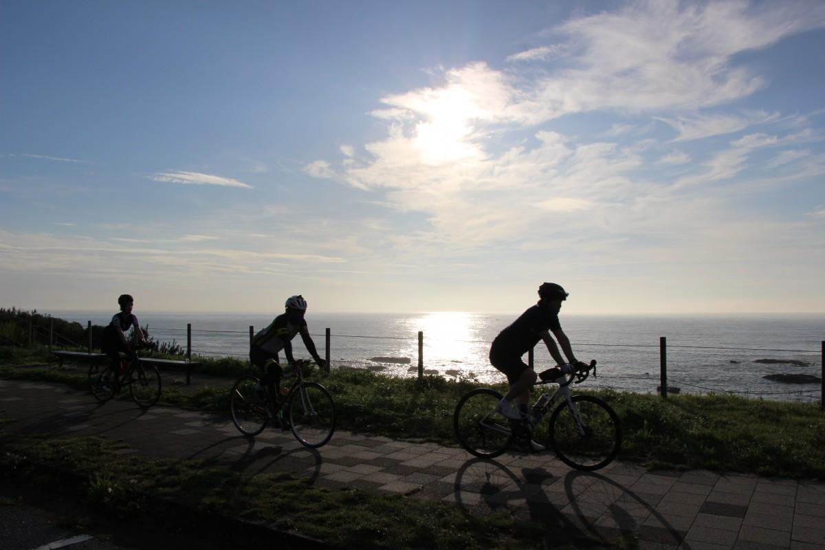 朝日を浴びてサイクリングをする参加者