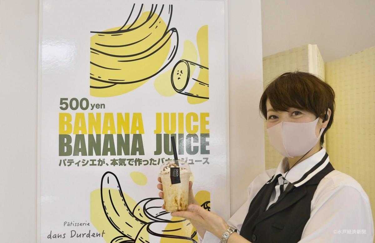 バナナジュースを持つ店長の藤井さん