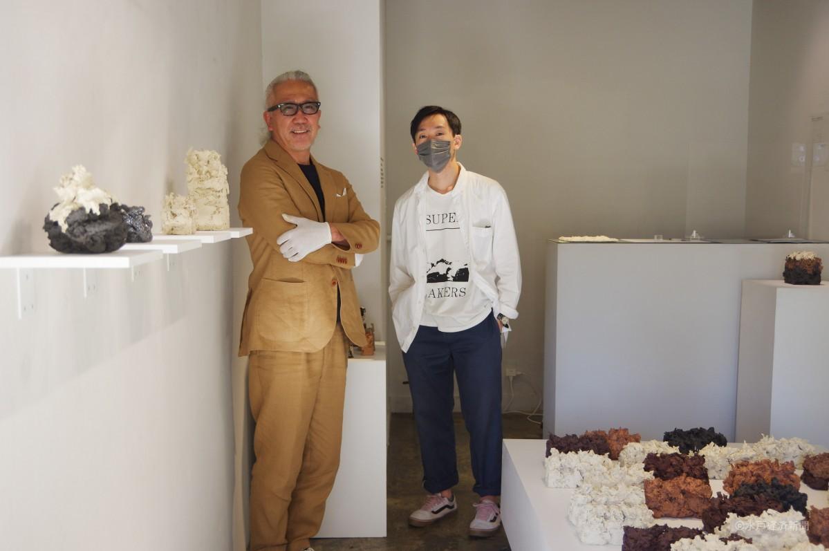 展示を前に立つ磯崎さんと展示スタッフ