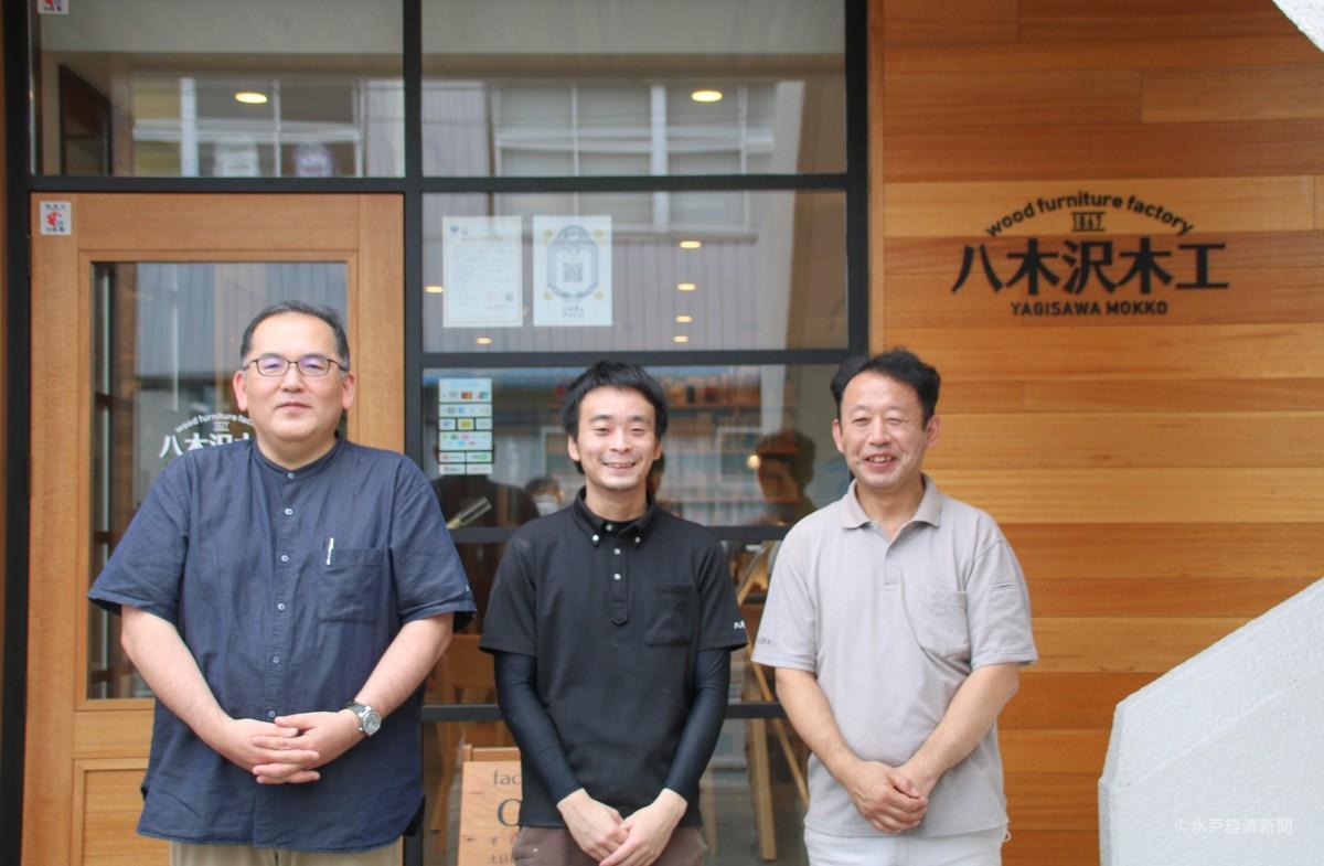 (左から)ファクトリーショップ前に立つ社長の八木沢さんとスタッフ