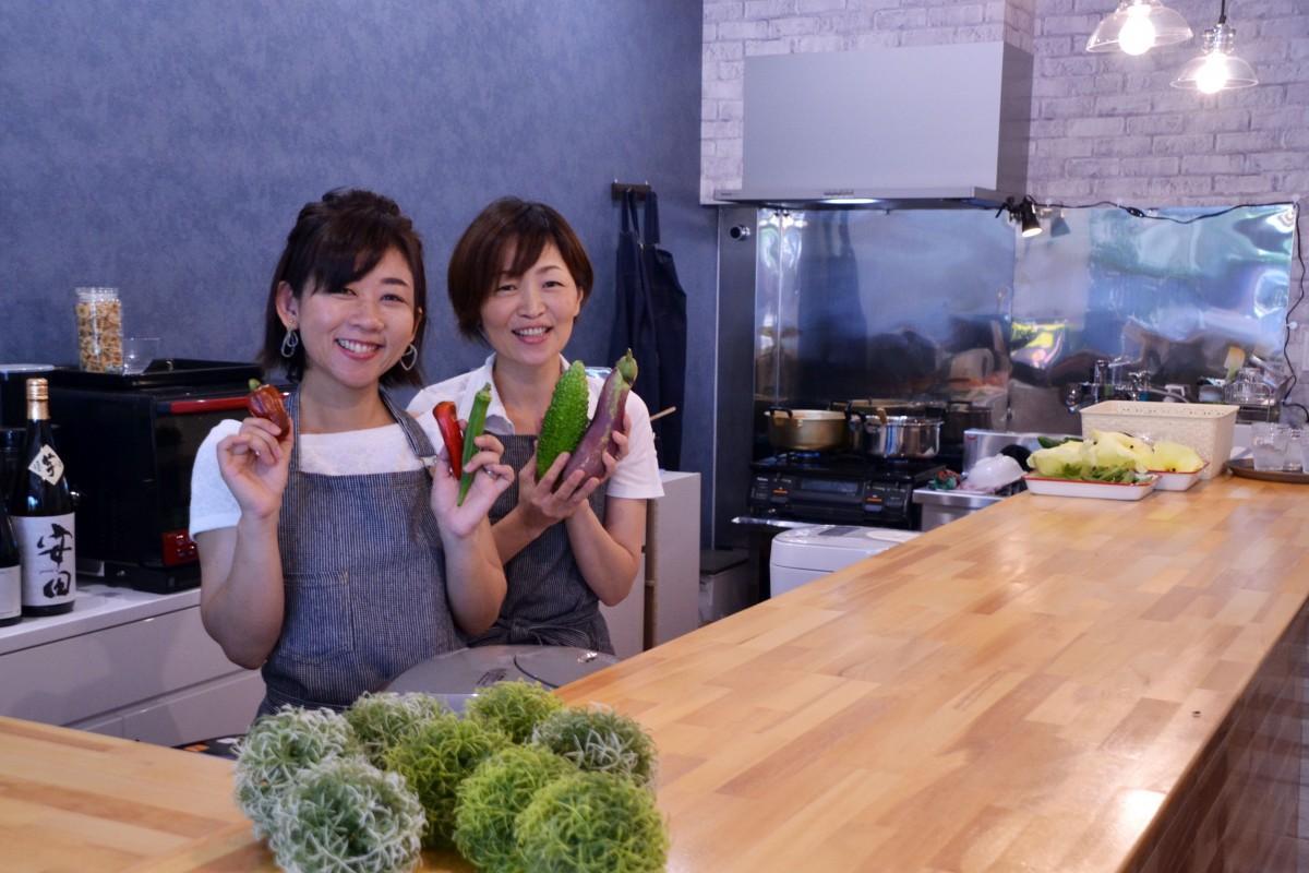 同町で採れた旬の野菜を手にする永住美香さん(左)とスタッフの小田典子さん(右)