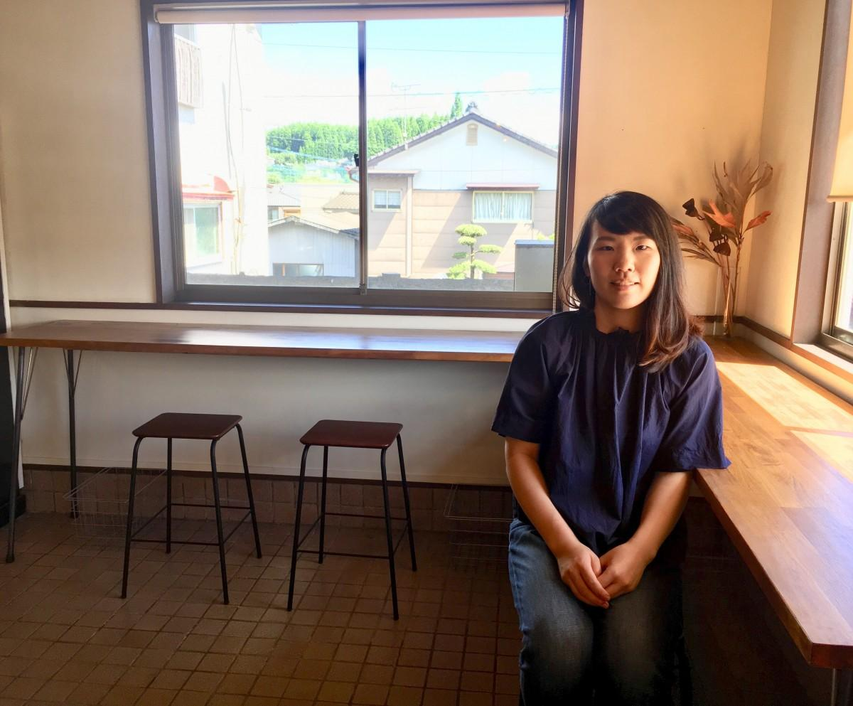 店主の上岡唯子さん、お気に入りの窓際のカウンターにて