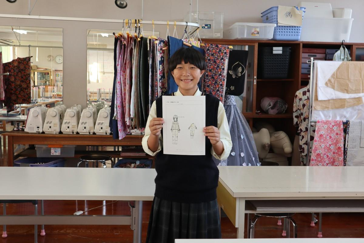 笑顔でデザイン画を持つ福井七海さん