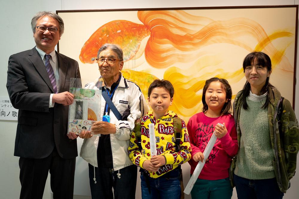 左からみやざきアートセンターセンター長の長岡政己さんと、来場者5000人目となった赤川さん一家